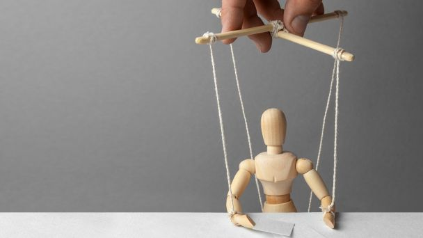 A hand controlling a marionette, representing a manager micromanaging employees.